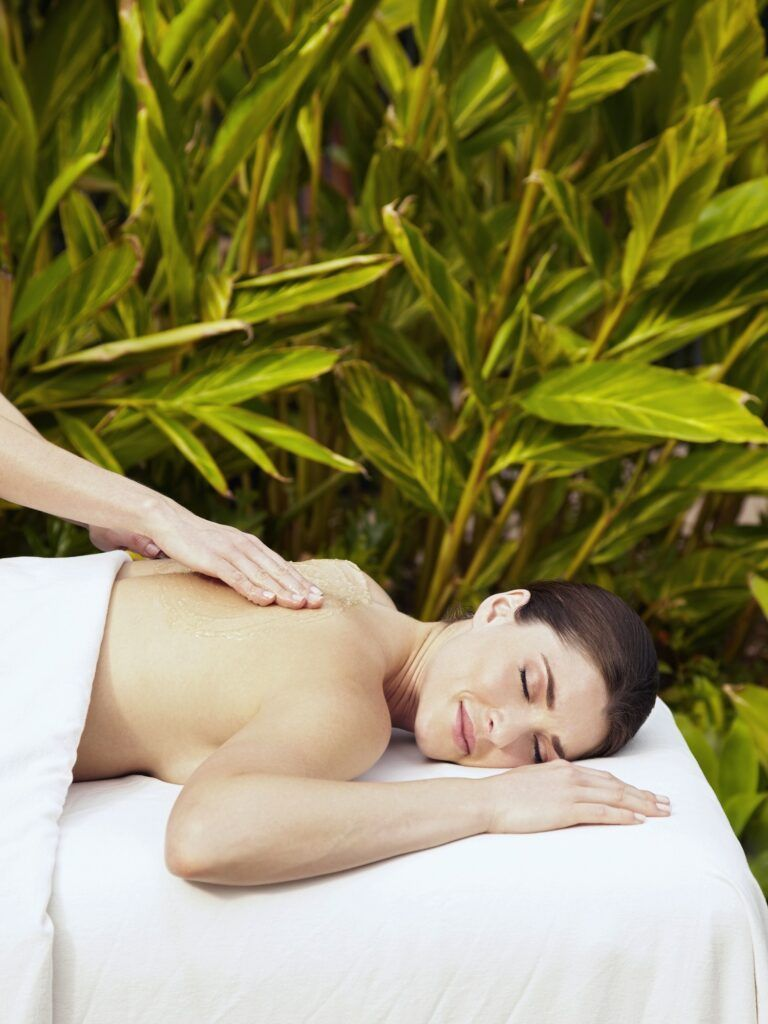 Caucasian woman getting massage with body scrub